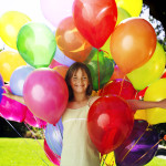Young Girl (10-11) Smiling Holding a Bunch of Balloons